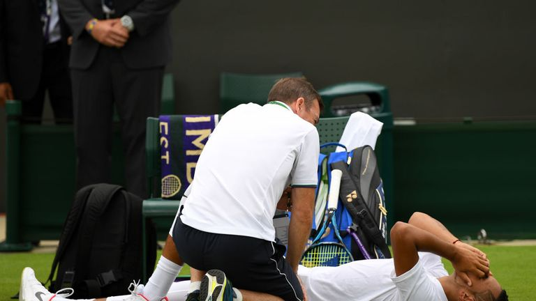 Kyrgios receives treatment during the match against Pierre-Hugues Herbert