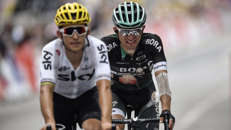 Rafal Majka crosses the line at the end of Sunday's stage with jersey torn and arm bandaged