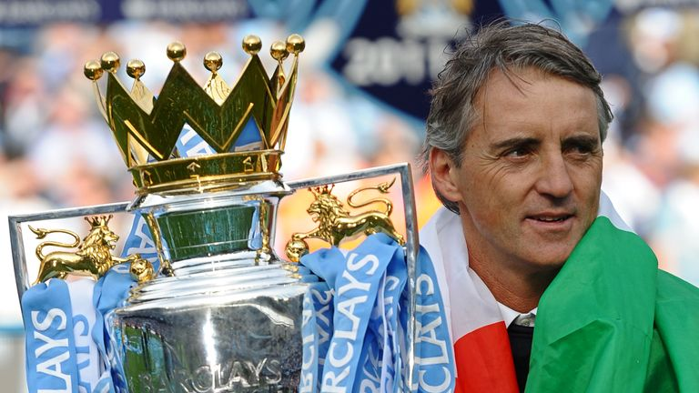 Manchester City's Italian manager Roberto Mancini celebrate with the Premier League trophy on the pitch after their 3-2 victory over Queens Park Rangers in