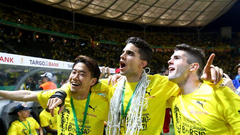 Shinji Kagawa, Marc Bartra and Christian Pulisic (L-R) celebrate after winning the DFB Cup final match between Eintracht Frankfurt and Borussia Dortmund