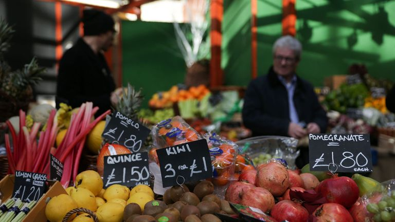 Signs display the price in pounds sterling of fruit and vegetables at a street market in southeast London, on February 14, 2017. British annual inflation p