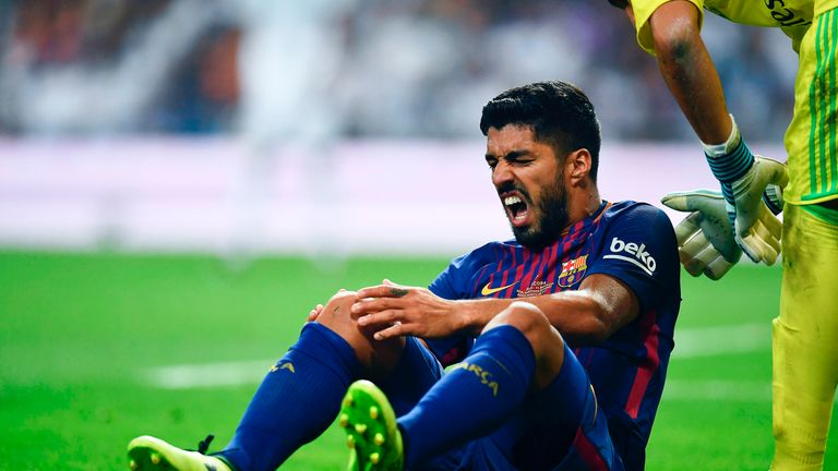 Luis Suarez grimaces while holding his knee during the Spanish Super Cup, Second Leg