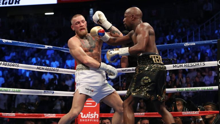Floyd Mayweather Jr. throws a punch at Conor McGregor during their super welterweight boxing match on August 26, 2017.