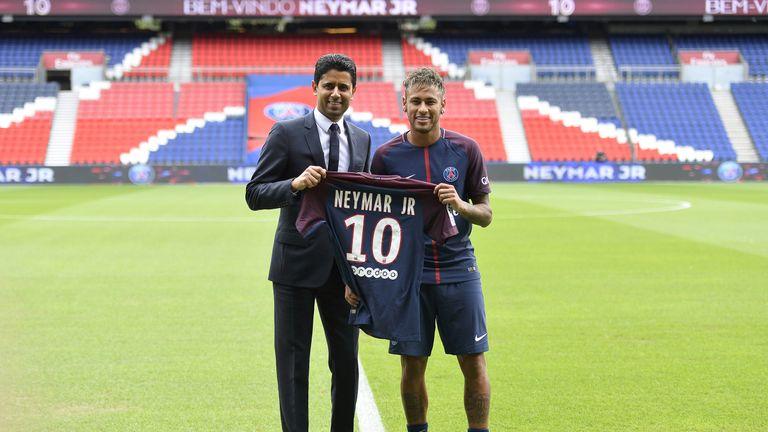 Neymar poses next to PSG President Nasser Al-Khelaifi after a press conference at Parc des Prince