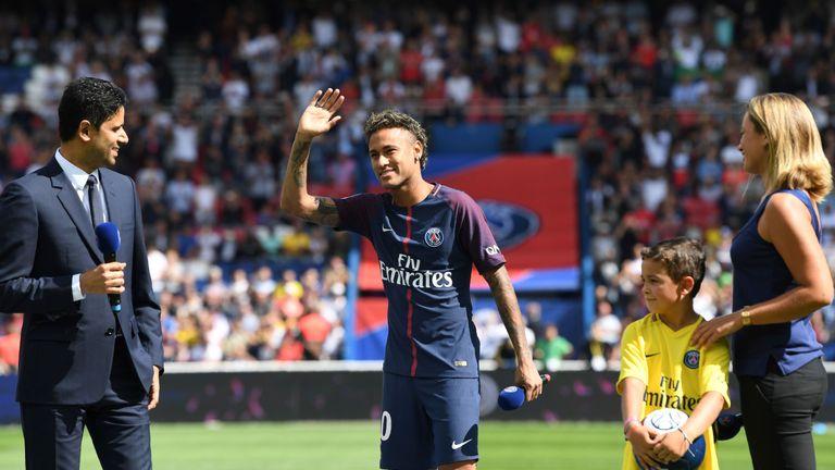 Paris Saint-Germain's Brazilian forward Neymar (C), flanked by Paris Saint Germain's (PSG) Qatari president Nasser Al-Khelaifi (L), waves to the crowd duri