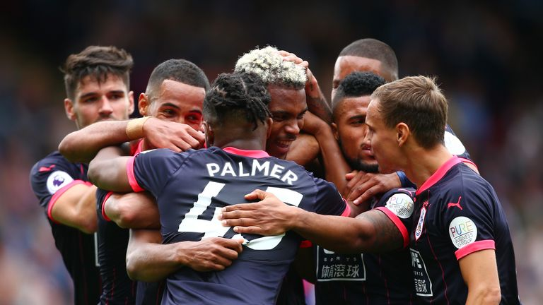 Steve Mounie is mobbed by team-mates after scoring Huddersfield's second goal