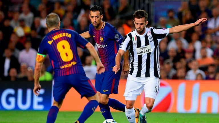 Barcelona midfielder Sergio Busquets (centre) battles for the ball with Juventus' Miralem Pjanic