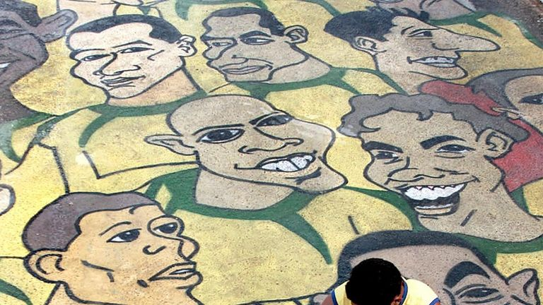 A man puts finishing touches to street art featuring the Brazil football team