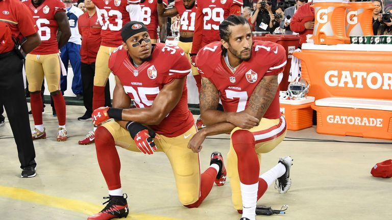 Colin Kaepernick #7 and Eric Reid #35 of the San Francisco 49ers kneel in protest during the national