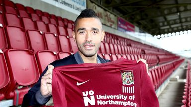 Lewis McGugan poses with a shirt during a photo call at Sixfields