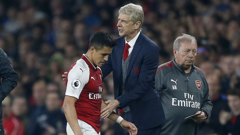 Arsenal's Chilean striker Alexis Sanchez passes Arsene Wenger as he substituted off of the pitch during the game v WBA on September 25, 2017