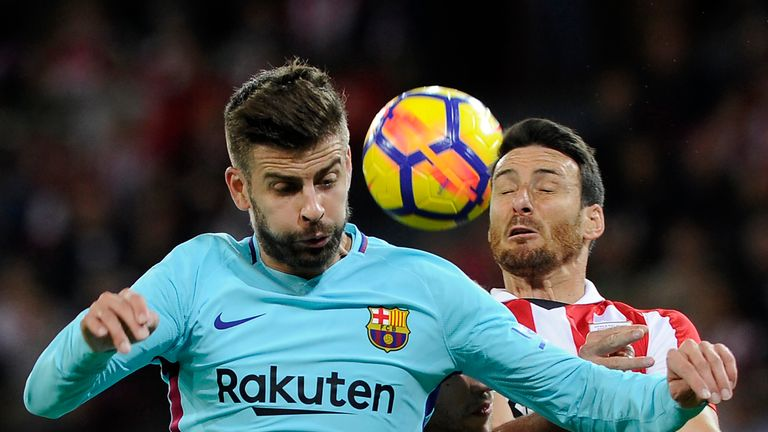 Gerard Pique wins the ball from forward Aritz Aduriz