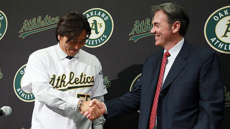 OAKLAND, CA - DECEMBER 14:  Hideki Matsui (L) shakes hands with Oakland Athletics general manager Billy Beane (R) after trying on his new jersey during a p