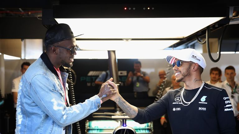 Usain Bolt shakes hands with Lewis Hamilton in the Mercedes F1 garage