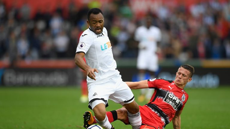 SWANSEA, WALES - OCTOBER 14:  Town player Jonathan Hogg fouls Jordan Ayew of Swansea and receives a yellow card for it during the Premier League match betw