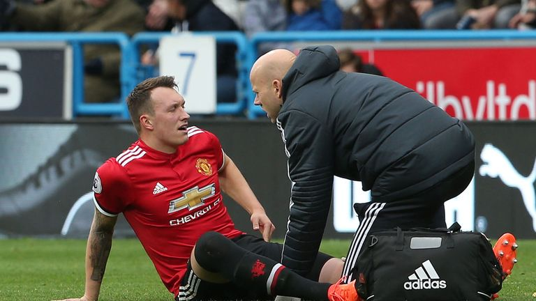 Jones receives treatment after picking up an injury during United's defeat at Huddersfield