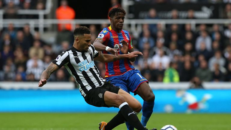 NEWCASTLE UPON TYNE, ENGLAND - OCTOBER 21:  Wilfried Zaha of Crystal Palace is tackled by Jamaal Lascelles of Newcastle United during the Premier League ma