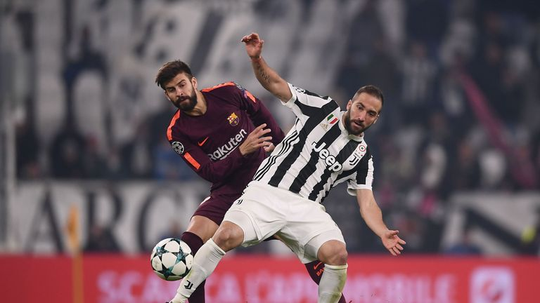 Barcelona defender Gerard Pique battles for the ball with Juventus Gonzalo Higuain