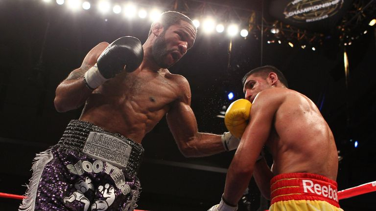 Lamont Peterson punches Amir Khan during their WBA Super Lightweight and IBF Junior Welterweight title fight in Washington.