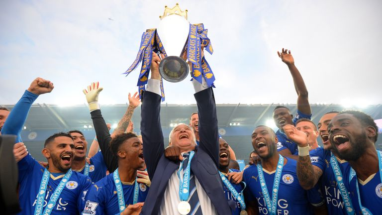 Claudio Ranieri Manager of Leicester City lifts the Premier League Trophy as players celebrate