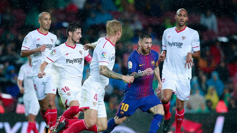 BARCELONA, SPAIN - NOVEMBER 04: Lionel Messi (R) competes for the ball with Simon Kjaer (3L) of Sevilla FC and his team mate Steven N'Zonzi (R) during the