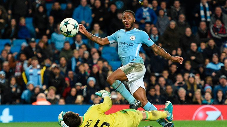 Raheem Sterling (R) lifts the ball over Feyenoord's Brad Jones (L) to score City's winner