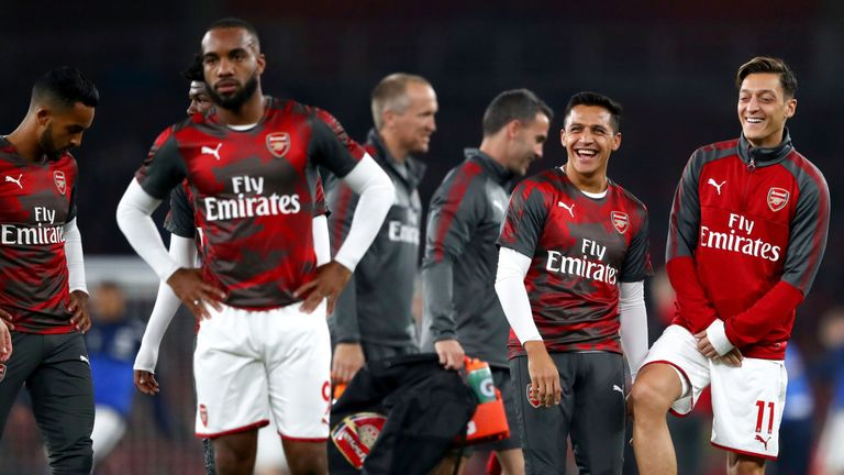 Alexis Sanchez and Mesut Ozil share a joke prior to the Premier League match between Arsenal and West Bromwich Albion on September 25, 2017