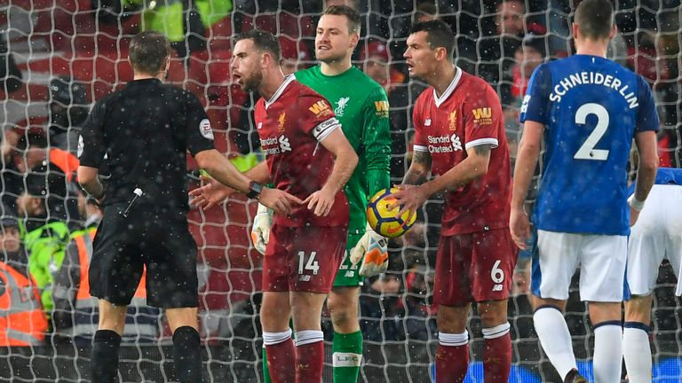 Jordan Henderson (2L) and Liverpool's Dejan Lovren (2R) talk with referee Craig Pawson (L) after Lovren conceded a penalty v Everton