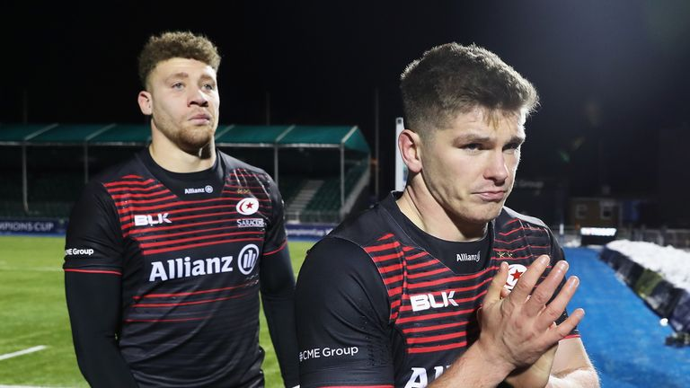Owen Farrell (R) of Saracens leaves the field dejected after the final whistle