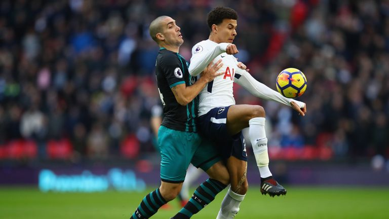 Dele Alli is challenged by Oriol Romeu at Wembley
