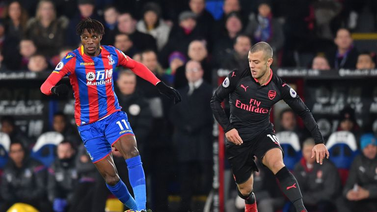 Wilfried Zaha (L) is tracked by Jack Wilshere