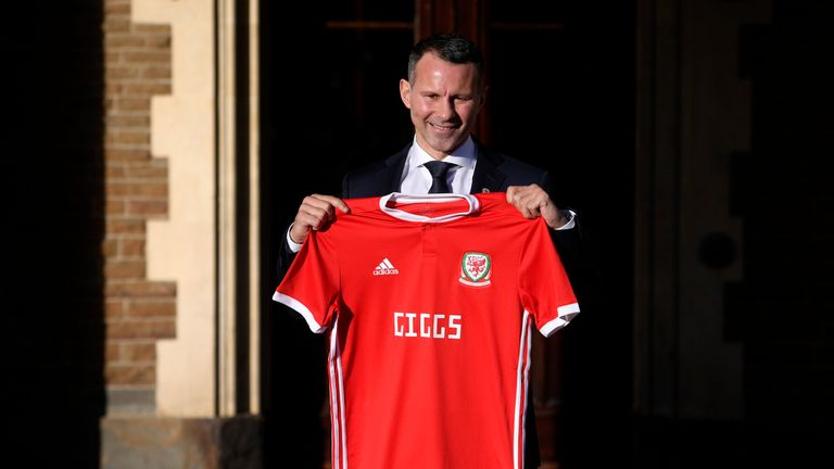 Ryan Giggs poses with a Wales shirt after being unveiled as new manager of the national team