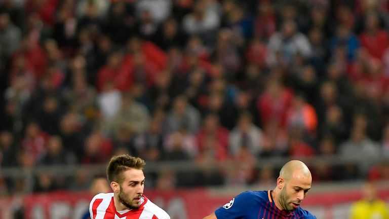 Olympiakos' midfielder Kostas Fortounis (L) vies with Barcelona's Argentinian defender Javier Mascherano  during the UEFA Champions League group D football