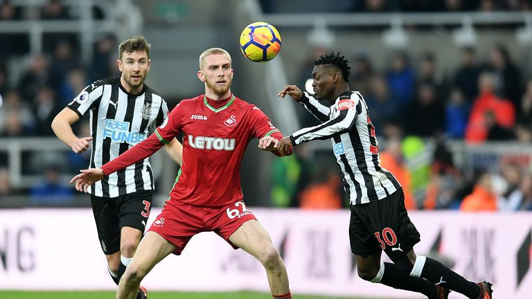 NEWCASTLE UPON TYNE, ENGLAND - JANUARY 13:  Christian Atsu of Newcastle United wins a header over Oliver McBurnie of Swansea City during the Premier League
