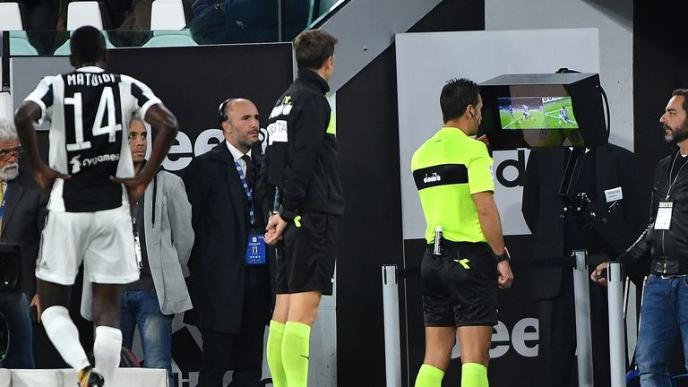 Referee Daniele Doveri (C) checks the VAR (video assistant referee) during the Italian Serie A football match Juventus vs Fiorentina on September 20, 2017