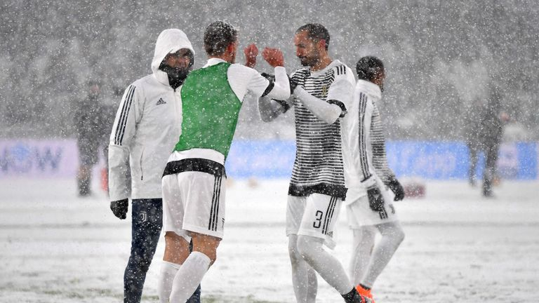 Juventus' players warm up under heavy snowfall