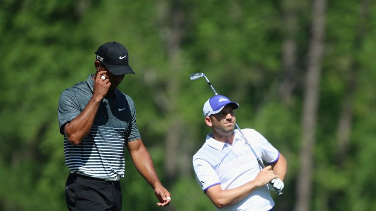 AUGUSTA, GA - APRIL 11:  Sergio Garcia of Spain watches his tee shot on the 12th hole as Tiger Woods of the United States looks on during the third round o