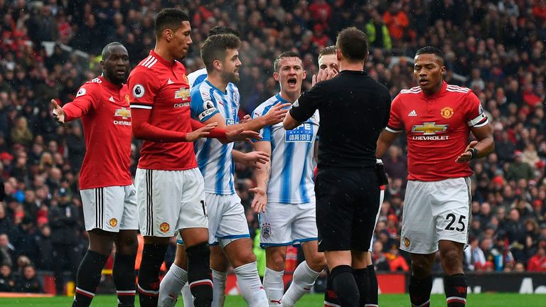 Players surround referee Stuart Attwell after the penalty appeal