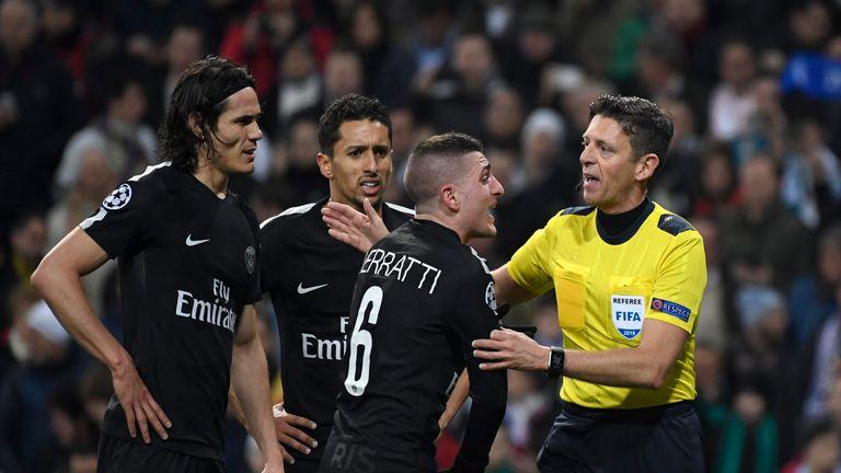 Paris Saint-Germain players argue with the referee