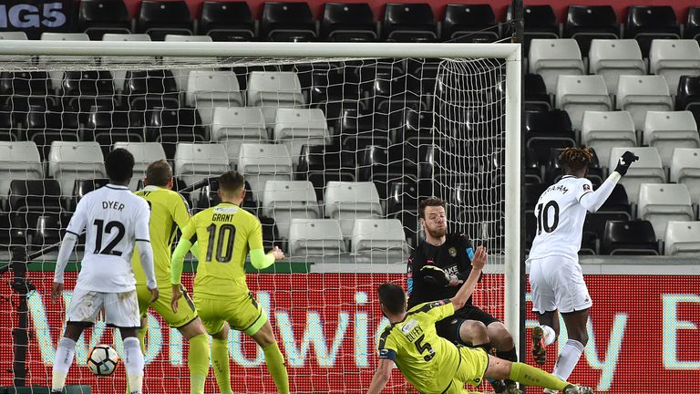 Swansea City's Tammy Abraham (right) scores his side's first goal during the Emirates FA Cup, fourth round replay match at the Liberty Stadium, Swansea.