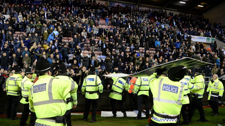 An advertising board is thrown at police as they attempt to prevent a pitch invasion after the Emirates FA Cup Fifth Round m