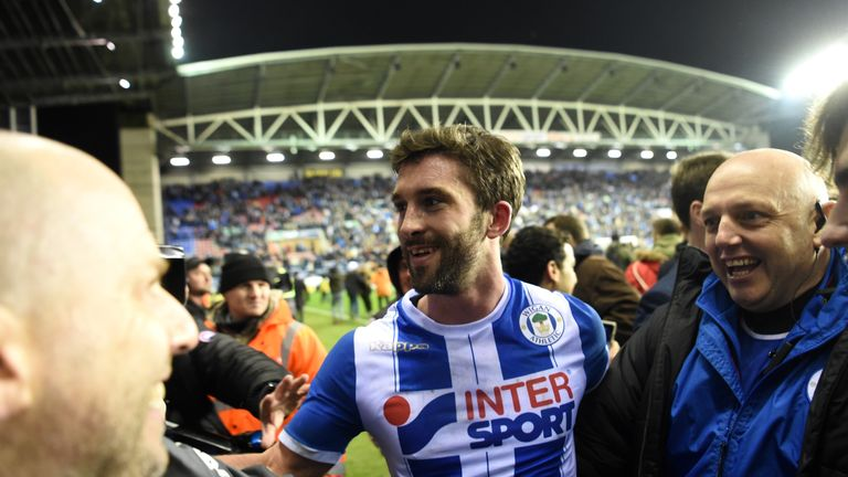 WIGAN, ENGLAND - FEBRUARY 19:  William Grigg of Wigan Athletic with fans on the pitch after the Emirates FA Cup Fifth Round match between Wigan Athletic an
