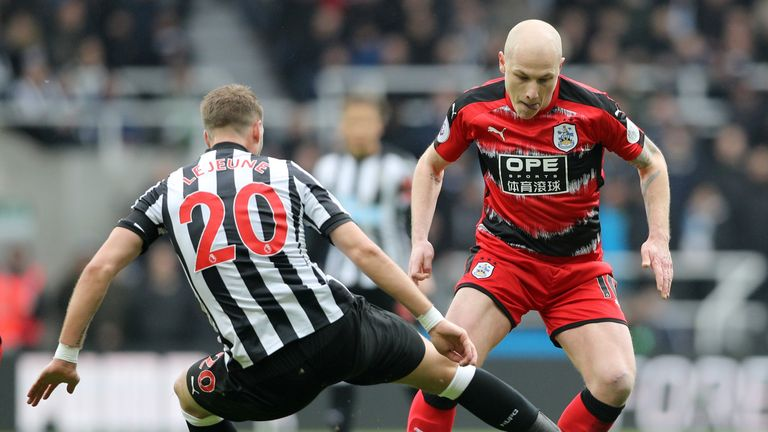 Newcastle United's Florian Lejeune challenges Huddersfield Town's Aaron Mooy