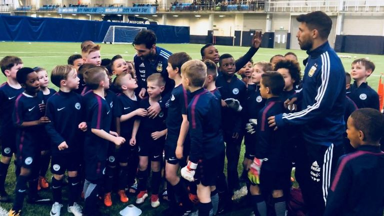 Messi offers academy youngsters some word of encouragement while Aguero watches on (photo: Manchester City)