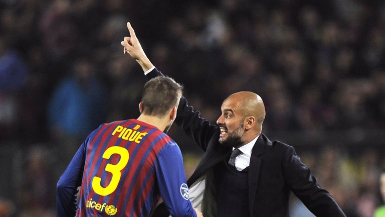 Pep Guardiola gives instructions while Gerard Pique looks onduring the Champions League quarter-final second leg football match FC Barcelona vs AC Milan on April 3, 2012
