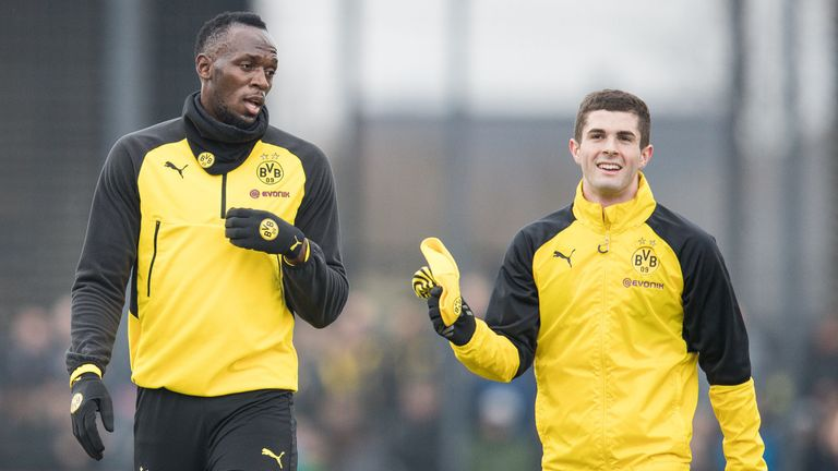 Usain Bolt talks to attacking midfielder Christian Pulisic during a Borussia Dortmund training session on March 23, 2018