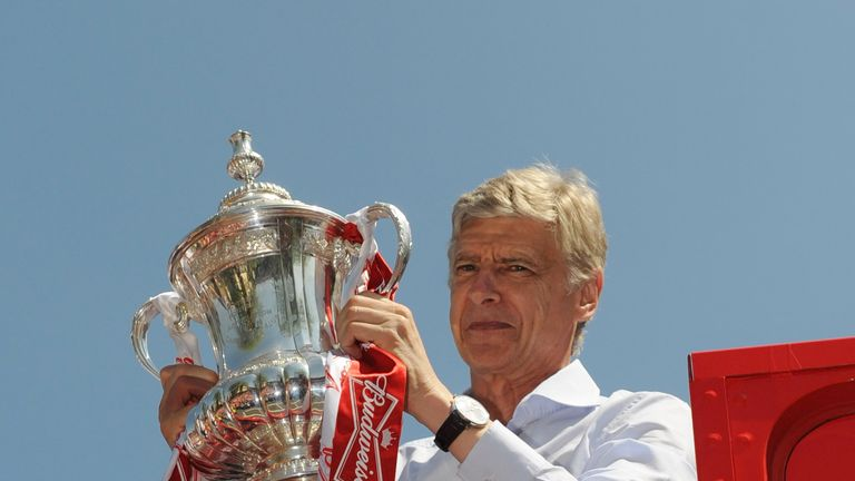 Arsene Wenger celebrates with the FA Cup onboard the Arsenal team bus during the FA Cup Victory Parade in Islington, London on May 18, 2014