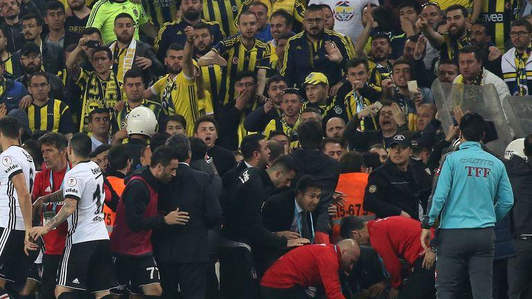 Besiktas head coach Senol Gunes received first aid on the pitch for a head injury