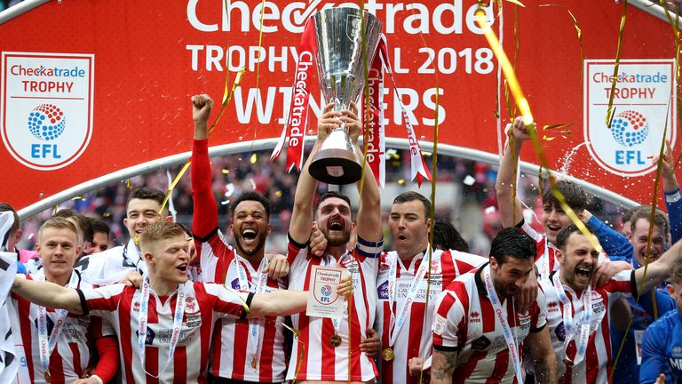 Lincoln City's players celebrate with the trophy after winning the Checkatrade Trophy final at Wembley