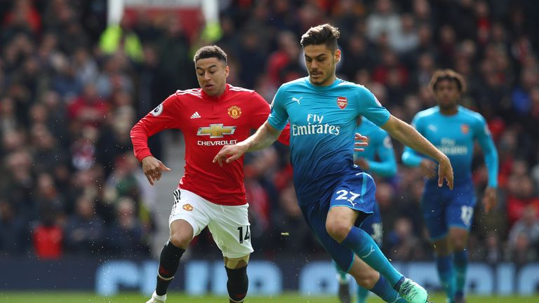 Konstantinos Mavropanos (R) is challenged by Jesse Lingard (L)